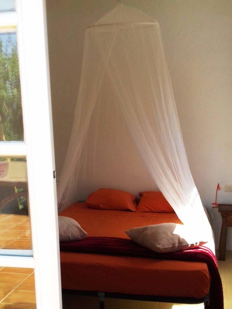 Casita ventana de la habitación, cama con mosquitera